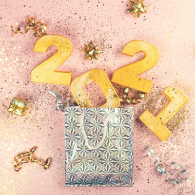 Happy New Year 2021. Digits 2021 are popping from the present bag. Holiday Party Decoration or postcard concept with top view and copy space.